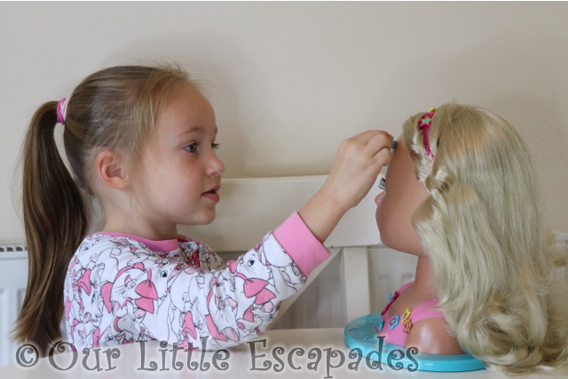 little e applying cat make-up baby born sister styling head