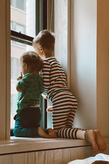two boys looking outside window